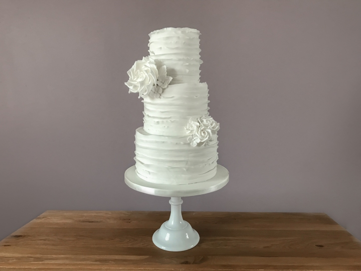 White wedding cake with ruffles and roses